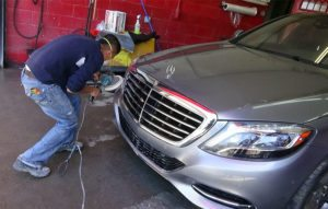 mechanic buffing mercedes bumper