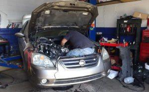 mechanic repairing a nissan engine