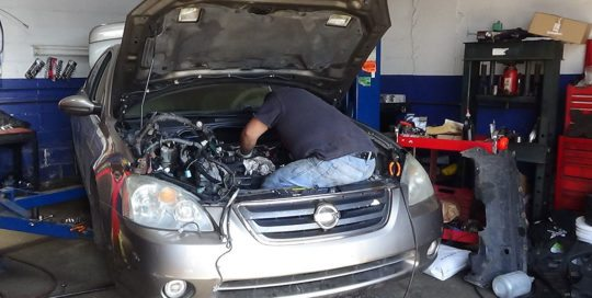 mechanic repairing a nissan engine